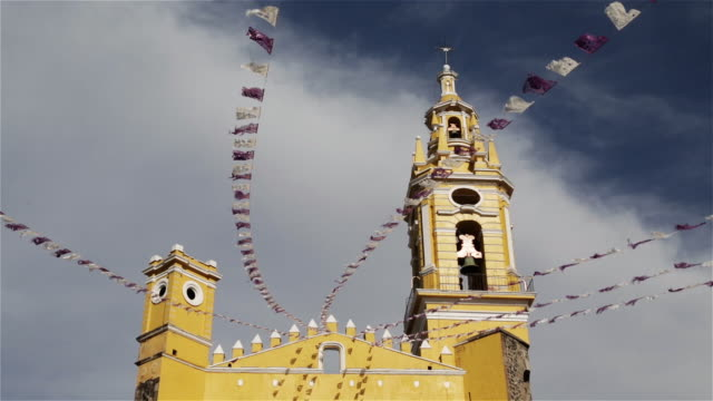 LS, LA Strings of flags fly outside a church / Puebla, Mexico