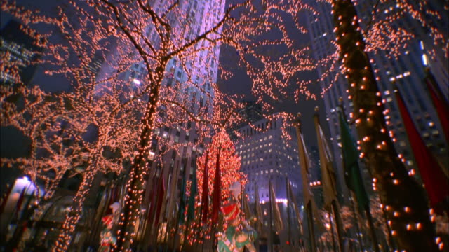strings of white lights decorate trees in rockefeller center. available in hd. - rockefeller center christmas tree stock videos & royalty-free footage