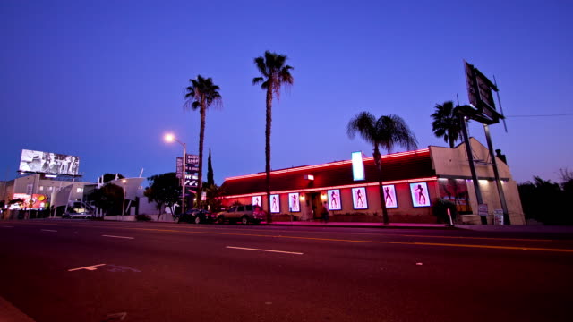 stockvideo's en b-roll-footage met zi t/l strip club on sunset strip at dusk with red neons and palm trees as traffic flows on sunset boulevard - west hollywood
