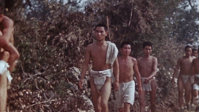stockvideo's en b-roll-footage met pan stripped japanese prisoners being escorted down a road by marines during world war ii a sherman tank and a jeep driving past / okinawa japan - gevangene