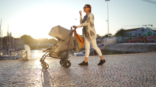 vídeos de stock, filmes e b-roll de passeando com seu bebê em lisboa perto do oceano - tourist