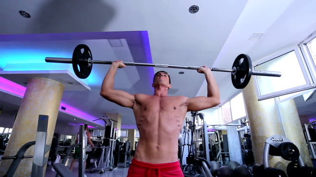 Strong, active and intense man lifting weights in gym