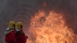 Strong and brave Firefighter on duty in Burning Building.Two firefighters fighting a fire with a hose and water during a firefighting