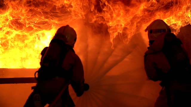 vídeos de stock e filmes b-roll de strong and brave firefighter on duty in burning building.two firefighters fighting a fire with a hose and water during a firefighting. - fogo