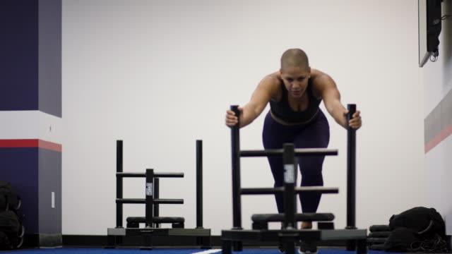 stockvideo's en b-roll-footage met een sterk en vastberaden etnische volwassen vrouwtje duwt een slee gewicht binnen een sportschool - fatcamera