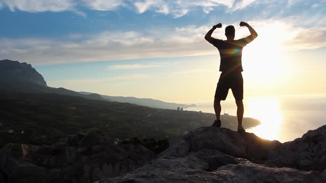 a strong and independent young man stands on top in a superhero or superman pose with raised hands and flexing arm muscles with clenched fists. human silhouette against the backdrop of a dramatic wilderness mountain landscape at dusk - human arm stock videos & royalty-free footage
