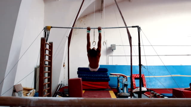 strong athlete performing routine on horizontal bar - horizontal bar stock videos and b-roll footage