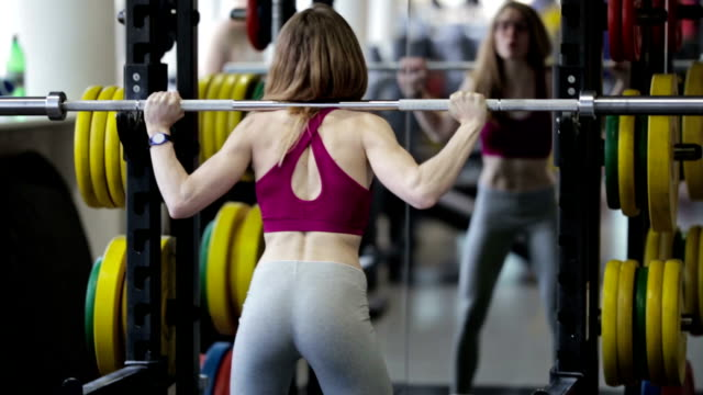 strong beauty young girl bodybuilder doing exercise in gym - sbarra da ginnastica video stock e b–roll