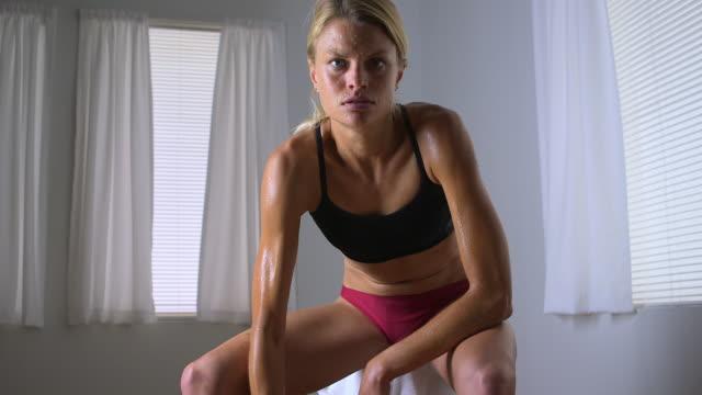 vídeos de stock e filmes b-roll de strong blonde woman lifting weights - fotografia de três quartos