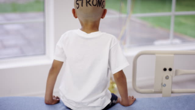 strong boy undergoing cancer treatment - completely bald stock videos and b-roll footage