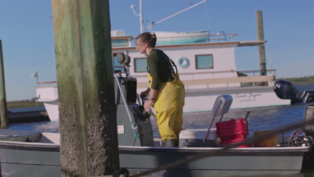 strong fisherwoman casts off docking lines and steers the boat through the marina to go harvest oysters and mussels. - incentive stock videos & royalty-free footage