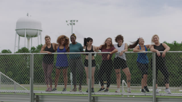 slow mo. strong group of fierce women stand at the top of a set of bleachers glaring at the camera and then start laughing - trainer stock videos & royalty-free footage
