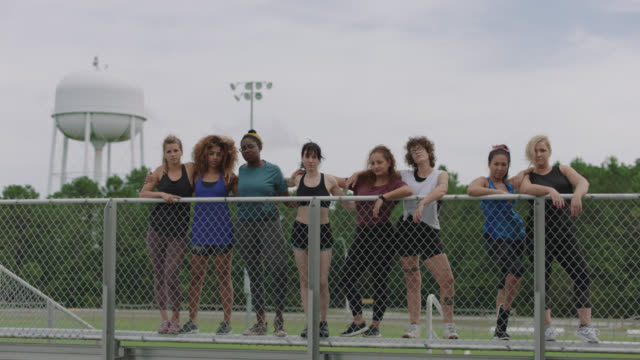 slow mo. strong group of fierce women stand at the top of a set of bleachers glaring at the camera and put their arms around each other - wire mesh fence stock videos & royalty-free footage