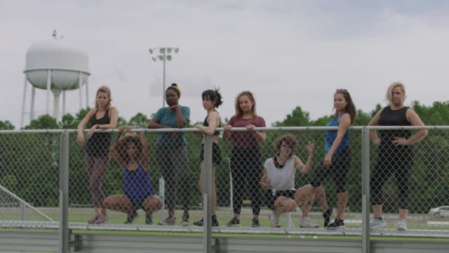 slow mo. strong group of fierce women stand at the top of a set of bleachers glaring at the camera - zaun stock-videos und b-roll-filmmaterial