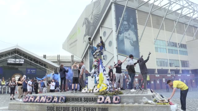 stockvideo's en b-roll-footage met 0008 and 112 120 leeds united fans celebrate outside elland road after west brom's loss to huddersfield confirmed their return to the premier league... - leeds