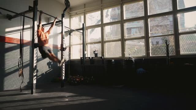 vídeos y material grabado en eventos de stock de hombre fuerte haciendo pull-ups mariposa en el gimnasio - entrenamiento sin material