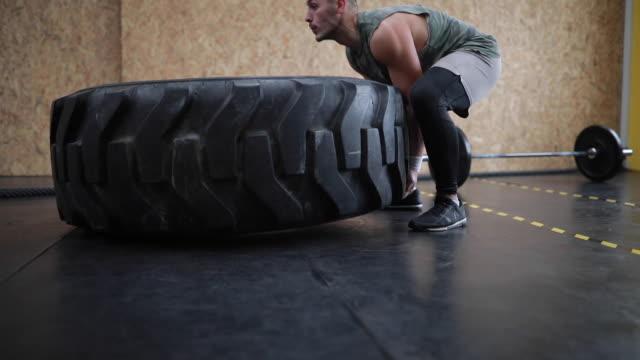 vidéos et rushes de homme fort faisant pneu retournant dans la salle de gym - soulever