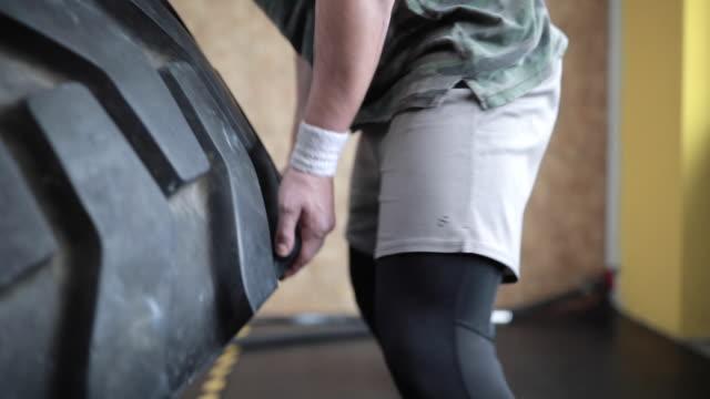 vidéos et rushes de homme fort faisant pneu retournant dans la salle de gym - entraînement croisé