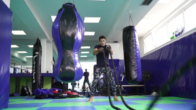 vídeos y material grabado en eventos de stock de hombre fuerte haciendo ejercicio con cuerdas de batalla - forzudo