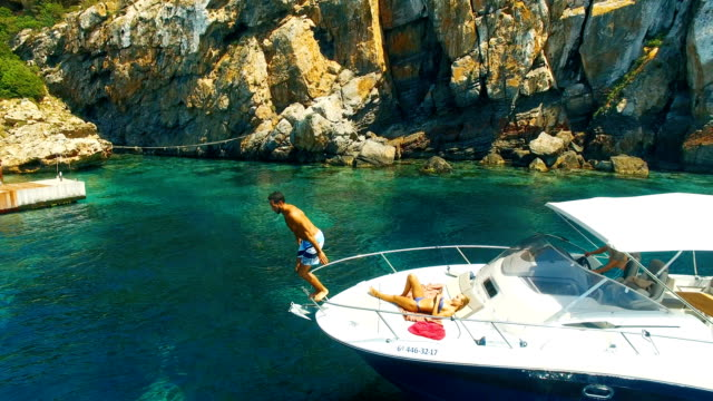 strong man jumping from a yatch in amazing, unspoiled and idyllic beach - segeljacht stock-videos und b-roll-filmmaterial