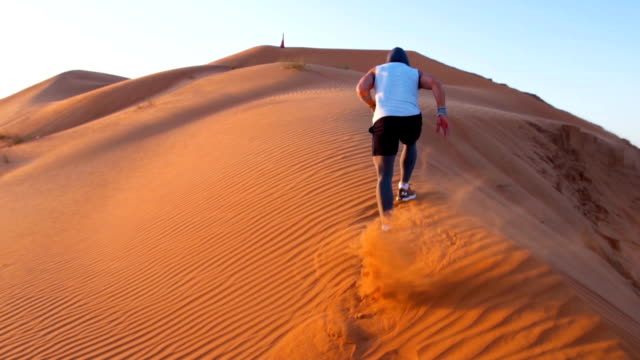 Strong man running upwards sand dunes