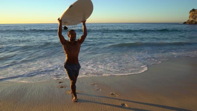vidéos et rushes de homme fort en rentrant à la plage sa planche de surf en haut - mouillé