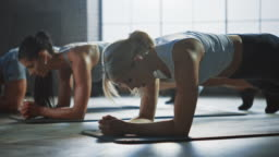 Strong Masculine Man and Two Fit Atletic Women Hold a Plank Position in Order to Exercise Their Core Strength. Blond Girl is Exhausted and Fails the Training First. They Workout in a Loft Gym.