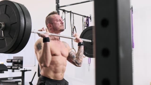 vídeos y material grabado en eventos de stock de hombre maduro fuerte levantamiento de pesas en el gimnasio local - un solo hombre de mediana edad