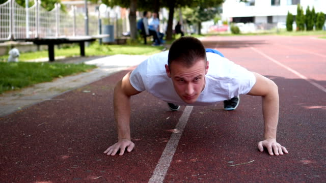 strong muscular fit young man exercise push-ups on the field - bodyweight training stock videos & royalty-free footage