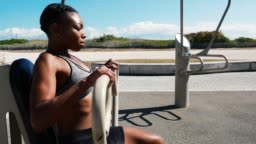 Strong muscular Hispanic or Afro Caribbean woman exercising near beach in summer in USA