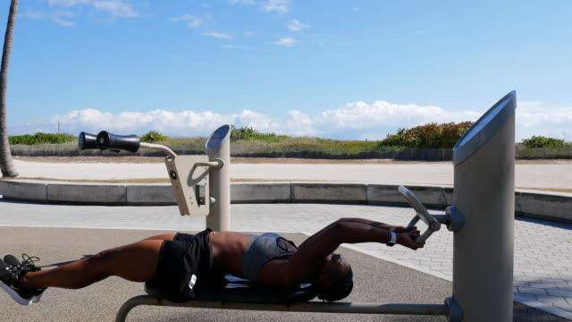 強い筋肉ヒスパニックやアフロカリブ海の女性は、米国の夏にビーチの近くで運動 - アフリカ系カリブ人点の映像素材/bロール