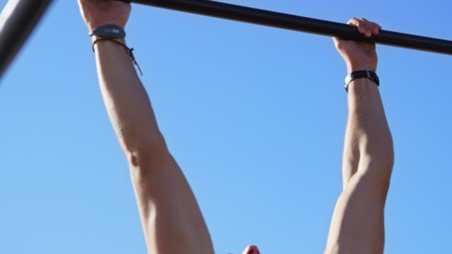 strong shirtless man practicing chin-ups at beach - sbarra da ginnastica video stock e b–roll