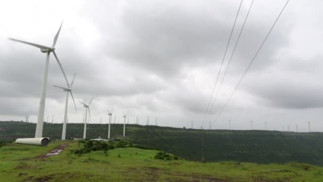Strong wind blows on a grassy knoll Spinning wind turbines stand on the top of a hill on an overcast day Close views of a wind turbine manufactured...