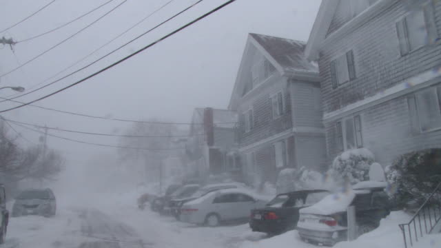 Strong winds and heavy snow combine to create near whiteout conditions on a residential street during a New England blizzard