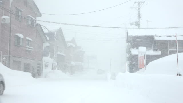 strong winds and heavy snow lash town during major blizzard in northern japan - 深い雪点の映像素材/bロール
