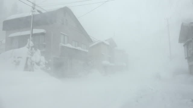 vídeos de stock, filmes e b-roll de strong winds and heavy snow lash town during major blizzard in northern japan - condições meteorológicas extremas