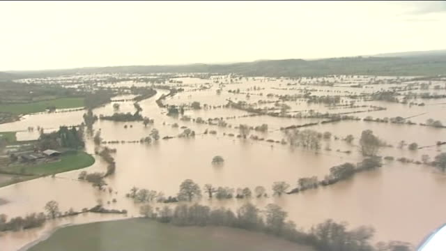 strong winds and more rain predicted to hit uk england gloucestershire flooded fields air view flooded river through town and fields air view... - gloucestershire stock videos and b-roll footage