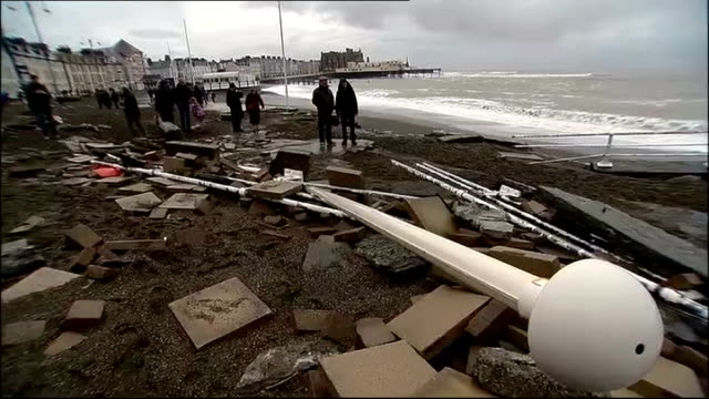 vídeos de stock, filmes e b-roll de strong winds and more rain predicted to hit uk wales aberystwyth people along on debris strewn beach with loose paving slabs and fallen lifering... - aberystwyth