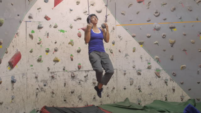 strong woman doing pull ups on suspension straps at a climbing wall site - chin ups stock videos and b-roll footage