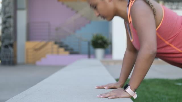 stockvideo's en b-roll-footage met sterke vrouw doet push ups workout - gras