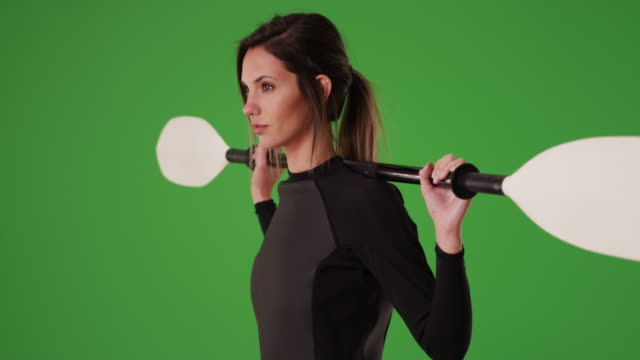 strong woman in wetsuit kayak paddle over shoulder facing side on greenscreen - wet wet wet stock videos & royalty-free footage