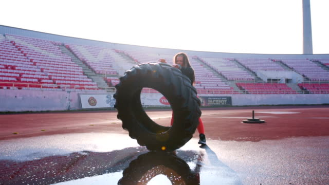 Strong woman lift heavy tire