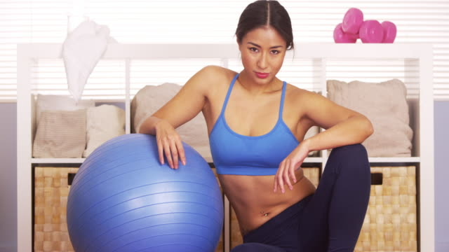 strong woman resting on exercise ball - one mid adult woman only stock videos & royalty-free footage