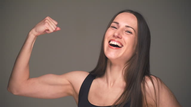 strong woman showing off bicep - bicep stock videos & royalty-free footage