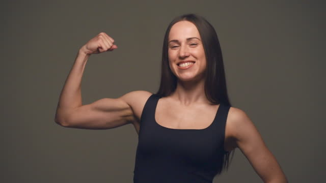 strong woman showing off biceps - muscular build stock videos & royalty-free footage