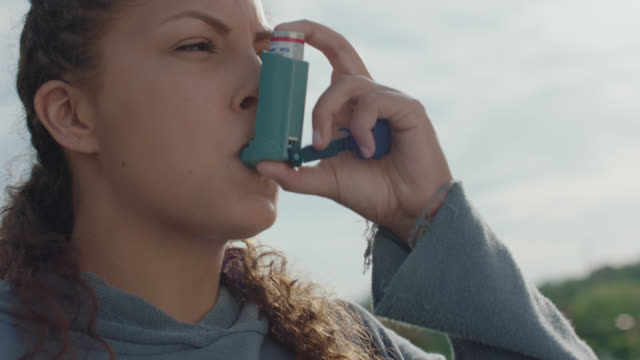 vidéos et rushes de cu. strong woman uses an inhaler on a set of bleachers before beginning her workout - inhaler