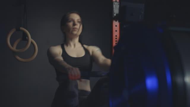 ガレージジムでボートマシンで働く強い女性。 - 自制心点の映像素材/bロール