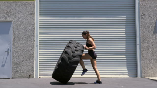 vidéos et rushes de ws strong woman working out with a giant tire - entraînement aux haltères