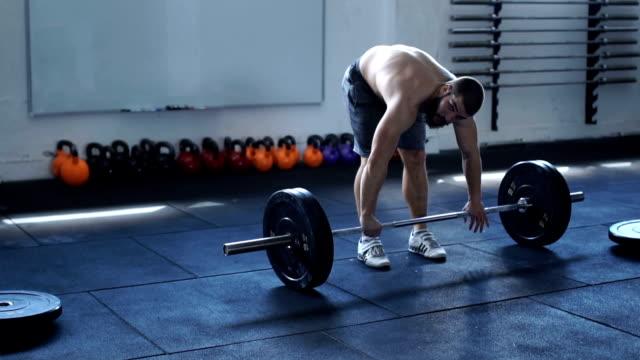 starker junger mann im fitness-studio - männlichkeit stock-videos und b-roll-filmmaterial