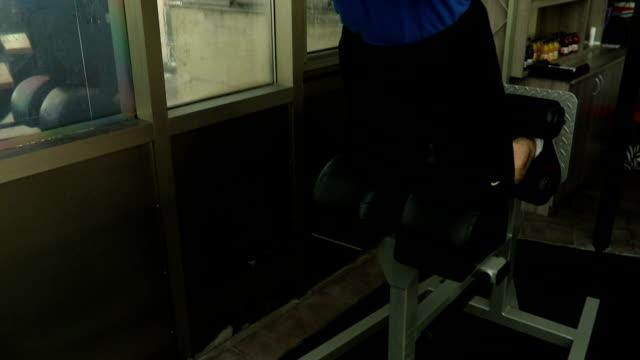 stockvideo's en b-roll-footage met sterke jonge mannen bodybuilder oefening in de sportschool doet - men